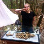 Archäologin mit Knochen im Wald.